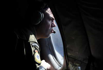 A crew member looks out an observation window aboard a RNZAF P3 Orion maritime search aircraft as it flies over the southern Indian Ocean looking for debris from missing Malaysian Airlines flight MH370