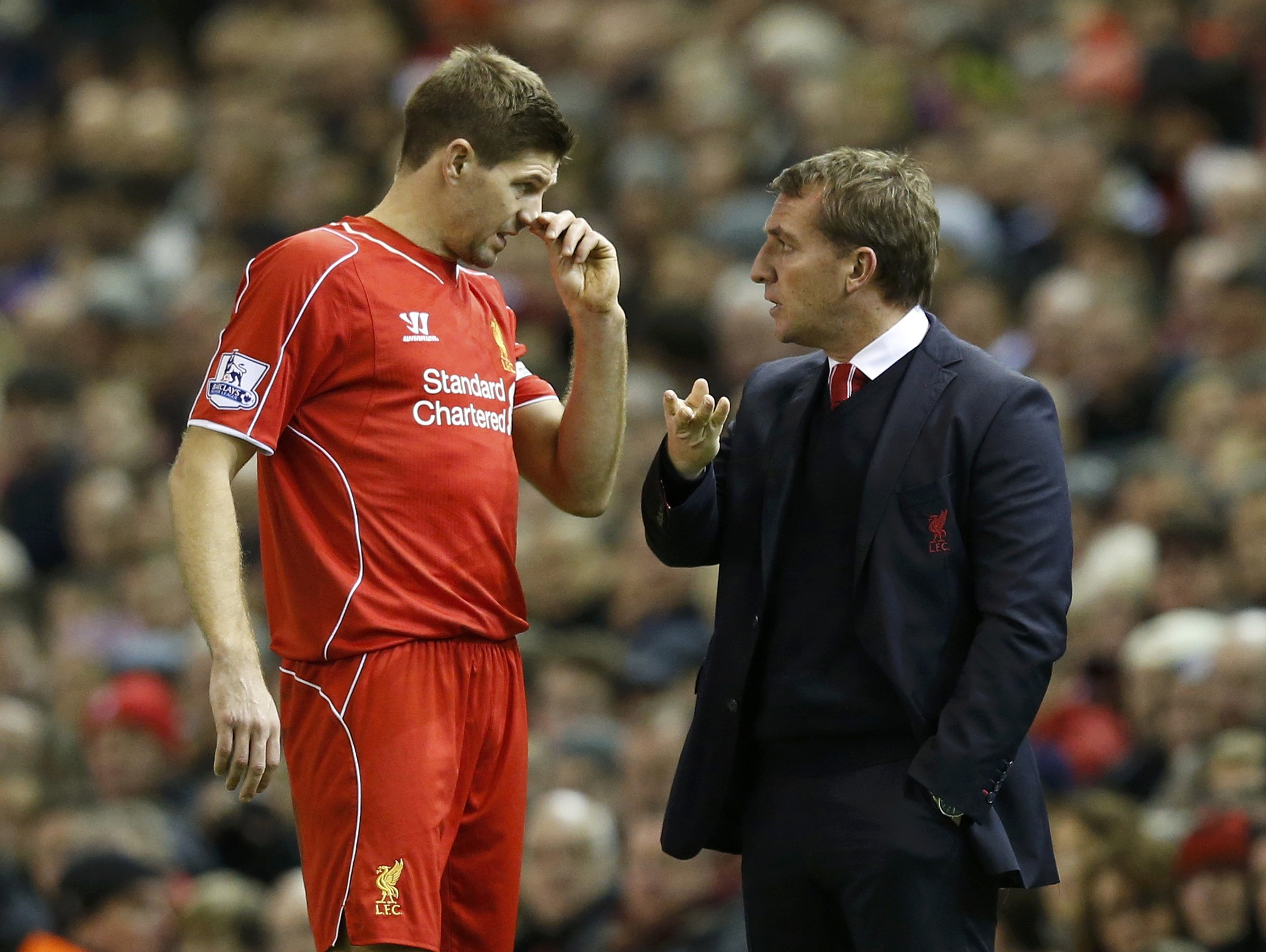 Liverpool manager Brendan Rodgers talks to Steven Gerrard during a break in their English Premier League soccer match against Arsenal at Anfield in Liverpool