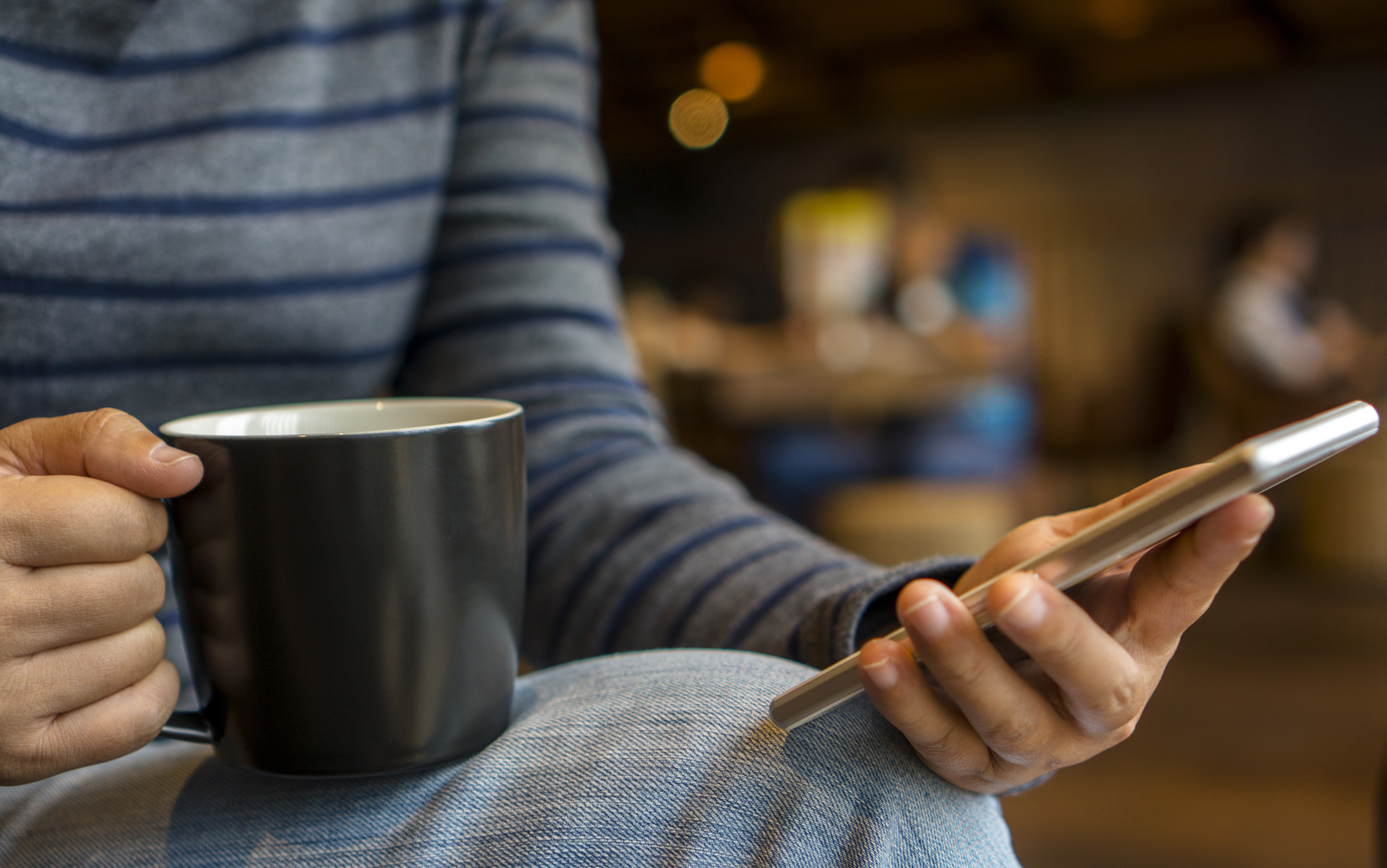girl reading smartphone while drinking coffee