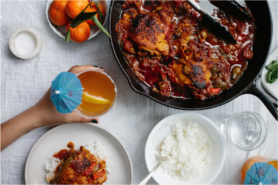 Pollo guisado and rice on a table with hand reaching out and holding citrus rum spritzer