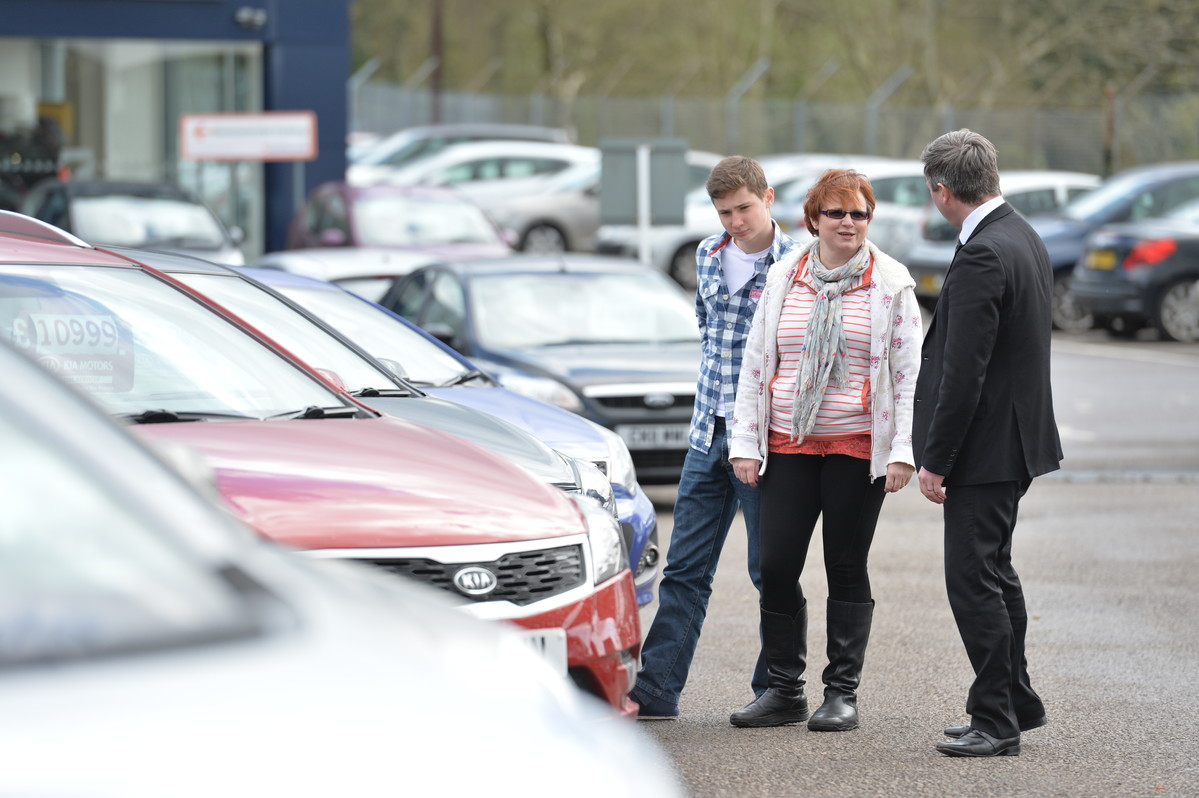 Mother and son talking to car dealer