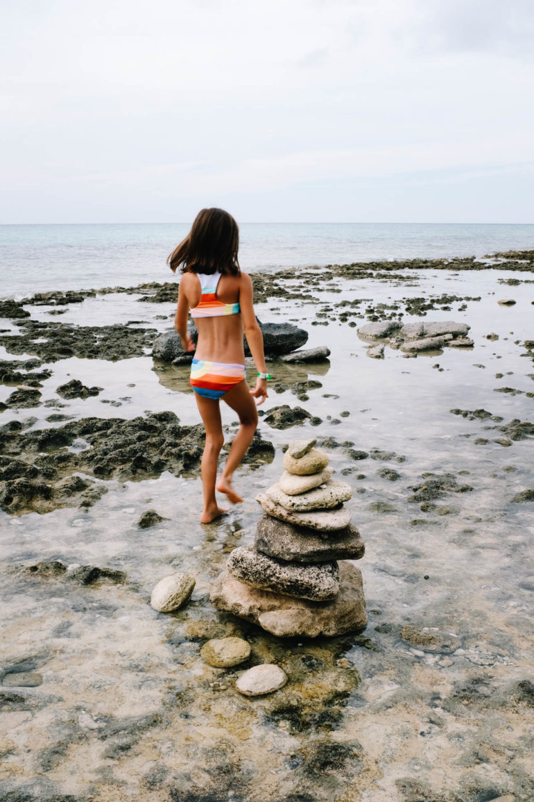daughter walking on rocky beach near small rock structure