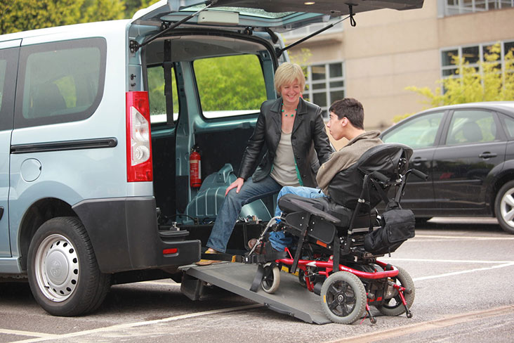 Man in wheelchair boarding Wheelchair Accessible Vehicle (WAV) using a ramp