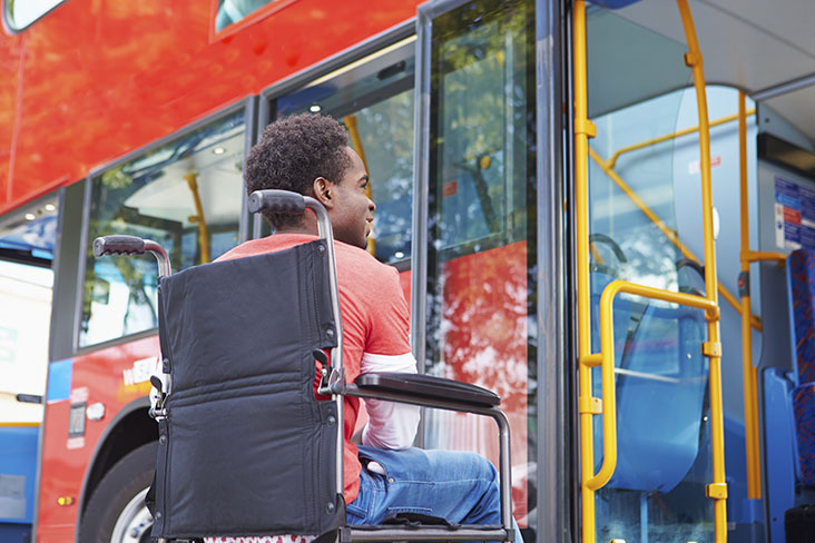 Man in wheelchair boarding a public bus